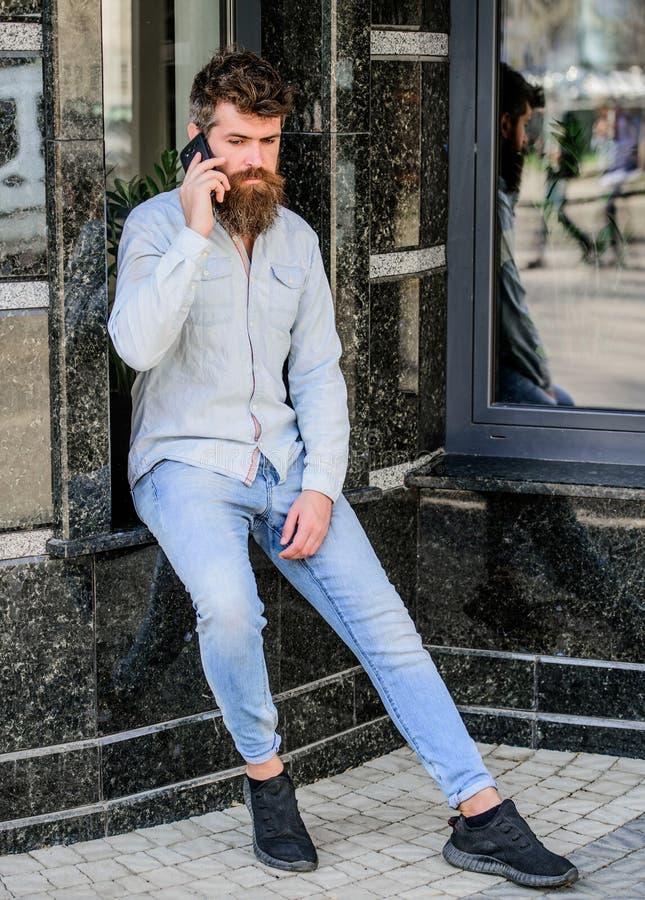 De greepsmartphone van de Hipstermens brutale zakenman met mobiele telefoon Gebaarde mens die op celtelefoon spreken gesprek en royalty-vrije stock foto