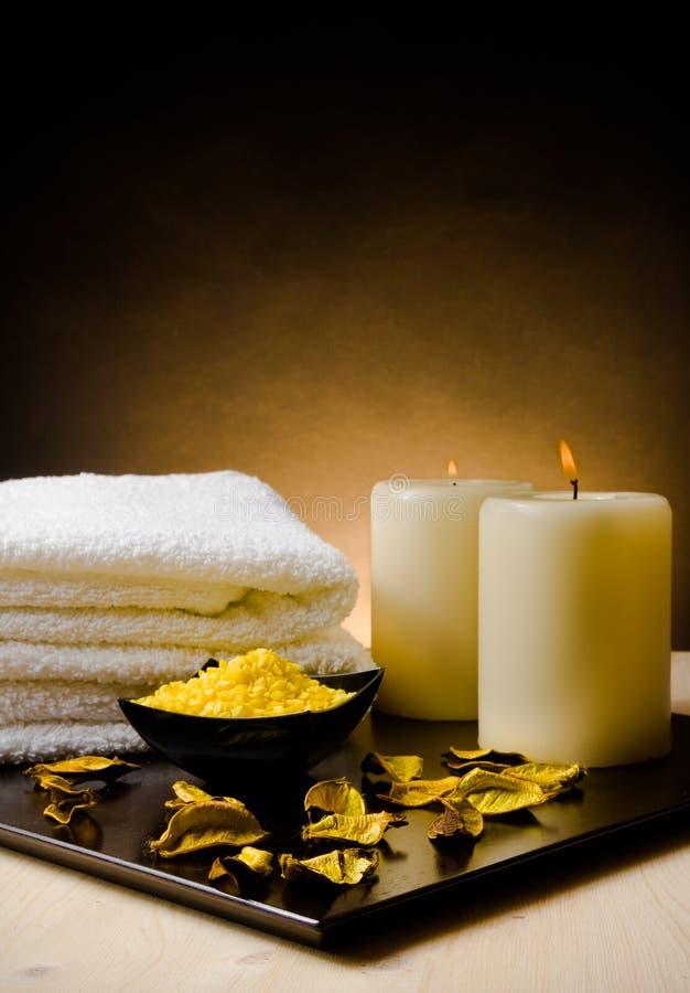 De grensachtergrond van de kuuroordmassage met gestapelde handdoek, geparfumeerde bladeren, kaars en overzees zout royalty-vrije stock foto