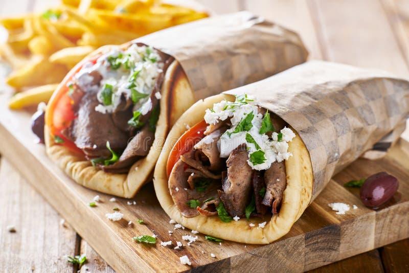 De Griekse gyroscopen van het lamsvlees met tzatzikisaus, feta-kaas en frieten stock afbeelding