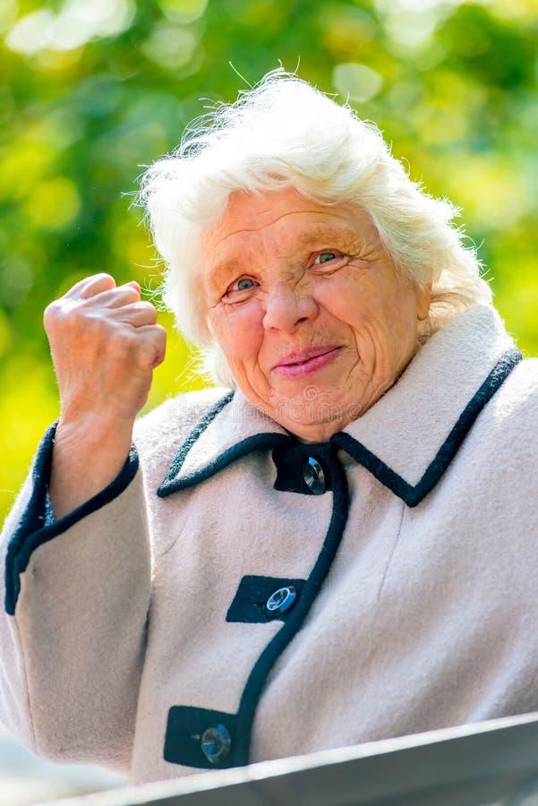 De grijs-haired oude dame toont een vuist royalty-vrije stock fotografie