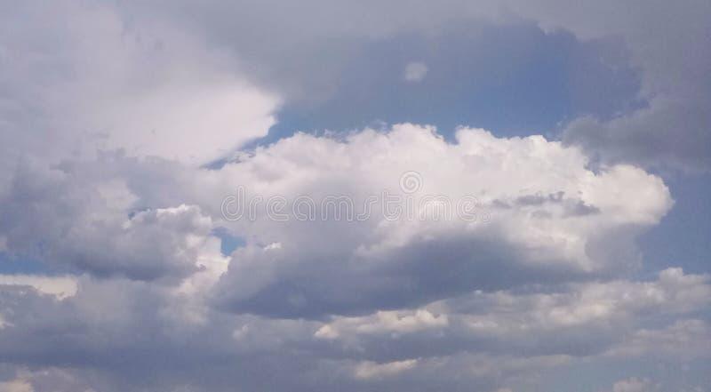 De grijs-witte wolken verduisteren de blauwe hemel royalty-vrije stock foto