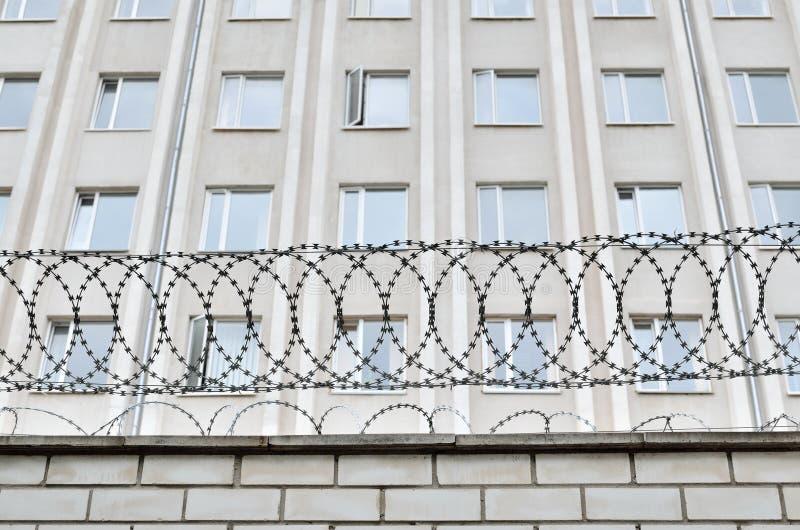 De grijze bouw is geschermd met prikkeldraad Symbool van dictatoriaal en autoritair regime royalty-vrije stock foto