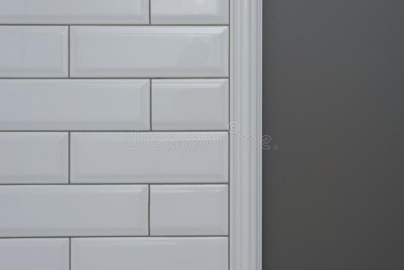 De grijze geschilderde muur, een deel van de muur is behandelde tegels kleine witte glanzende baksteen, ceramische decoratieve vo royalty-vrije stock fotografie