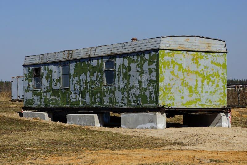 De grijze groene oude metaalcontainer met vensters bevindt zich in droog gras op een gebied royalty-vrije stock afbeelding