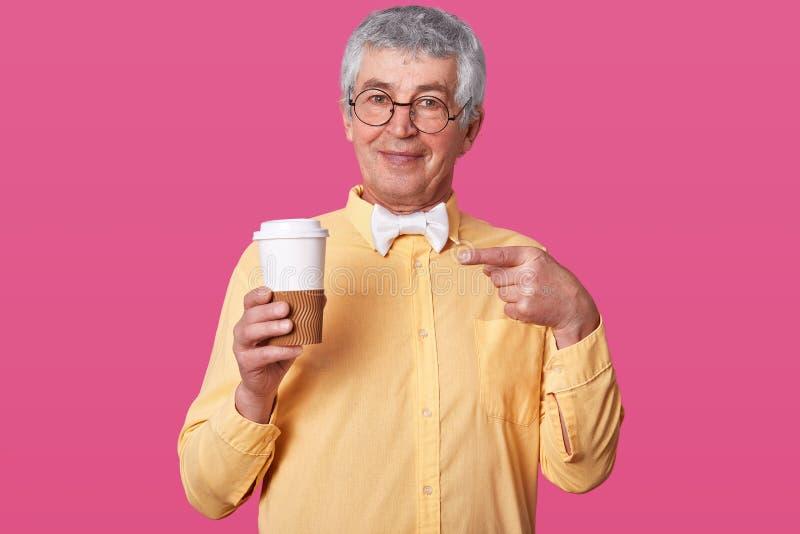 De grijze haired oudste in helder overhemd en bowtie houdt grote kop van koffie Bejaardetribunes met bril tegen studiomuur stock fotografie
