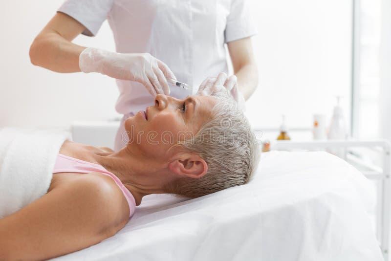 De grijze haired vrouw die van Nice een voorhoofd botox injectie ontvangen royalty-vrije stock afbeeldingen