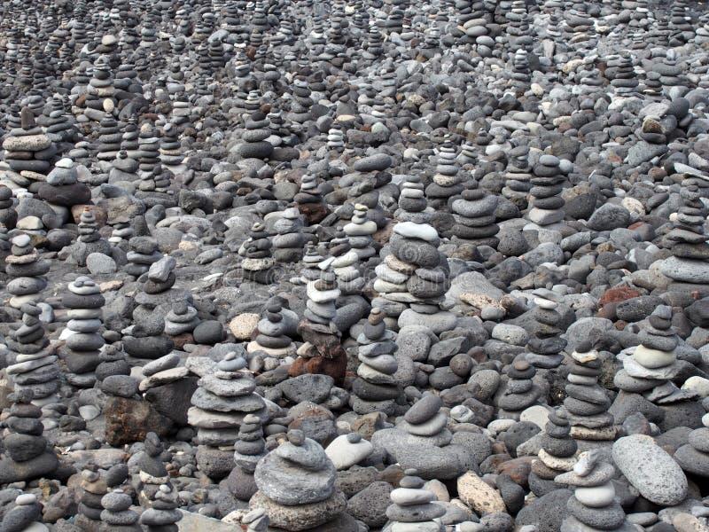 De grijze kiezelstenen en de stenen op een strand schikten in een grote inzameling die van stapels en torens het kader vullen royalty-vrije stock fotografie