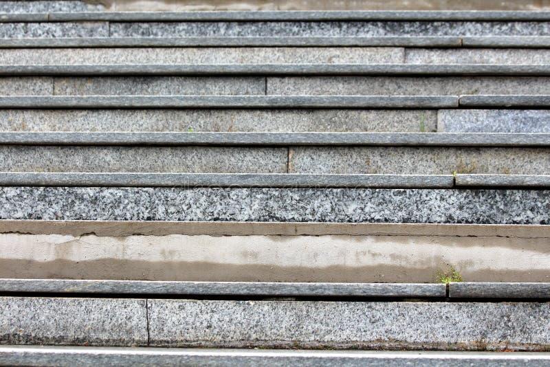 De grijze marmeren textuur van de tegelstrap met gevallen gebarsten tegels en zichtbare concrete stichting royalty-vrije stock foto's