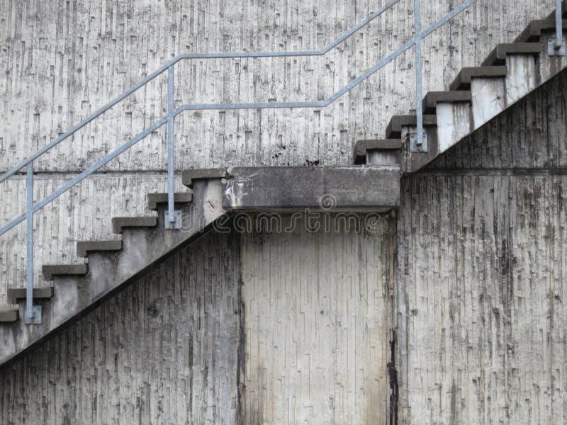 De grijze muur van de cementsteen met stappen en traliewerk royalty-vrije stock fotografie