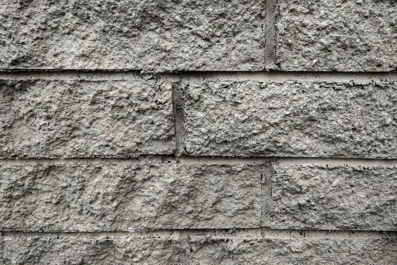 De grijze muuroppervlakte gebruikt heel wat bakstenen Of oud zwart bakstenen muur abstract patroon stock afbeelding