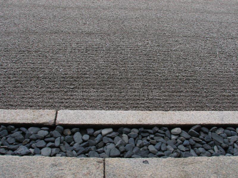 De grijze stenen en de fijn geharkte kuil van Zen Garden in Kyoto - JAPAN stock foto