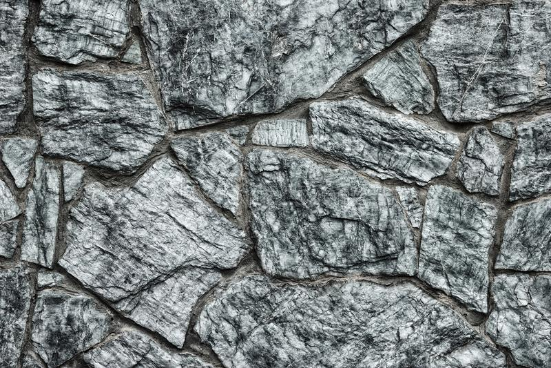 De grijze textuur van de steenmuur - de donkere gotische achtergrond van het rotsmetselwerk stock foto