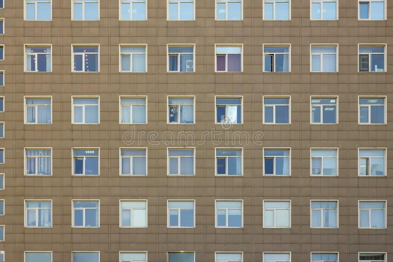 De grijze voorgevel van een high-rise bureaugebouw met meerdere verdiepingen met witte blauwe vierkante vensters royalty-vrije stock foto
