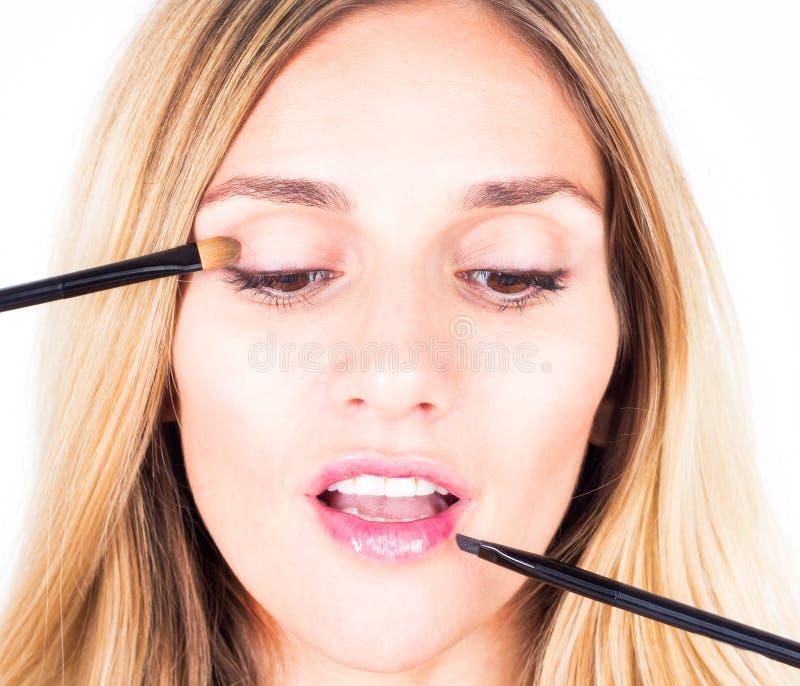 De grimeur die schaduwen toepassen en glanst met kosmetische borstels Sluit omhoog stock afbeelding