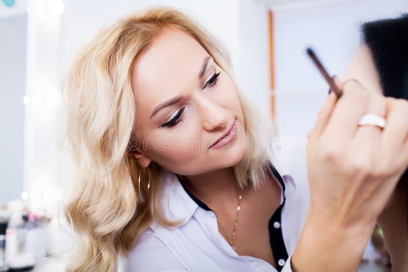 De grimeur doet make-up aan een mooi meisje in een schoonheidssalon royalty-vrije stock afbeeldingen