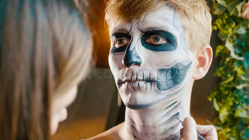 De grimeur maakt de kerel Halloween omhoog maken Mannelijk het gezichtsart. van Halloween stock foto's