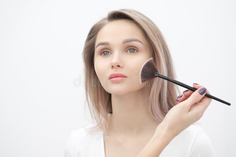 De grimeur maakt tot make-up mooi blondemeisje op een witte achtergrond Close-uphanden met borstel en gezicht stock afbeelding