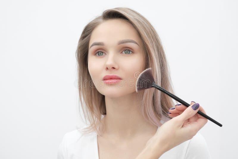 De grimeur maakt tot make-up mooi blondemeisje op een witte achtergrond Close-uphanden met borstel en gezicht stock foto's