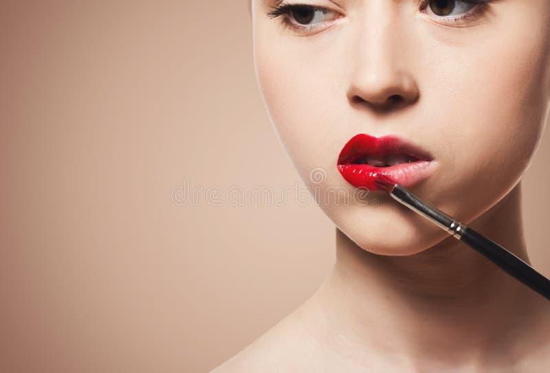 De grimeur past lippenstift met borstel, schoonheid toe royalty-vrije stock fotografie