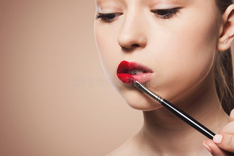 De grimeur past lippenstift met borstel, schoonheid toe stock foto's