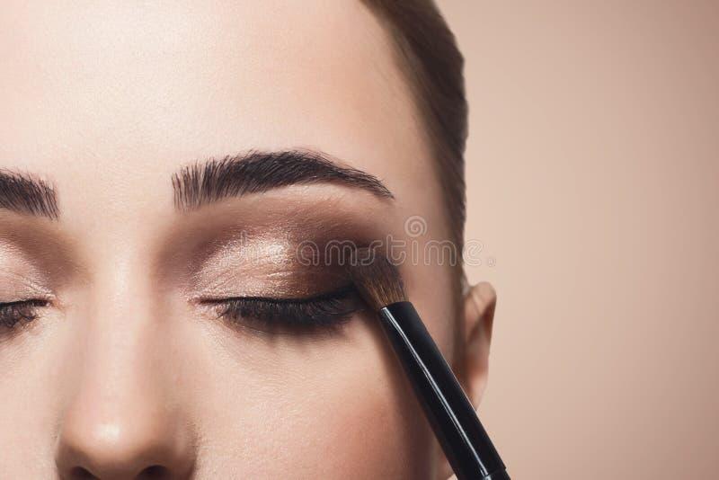De grimeur past oogschaduw met borstel, schoonheid toe royalty-vrije stock afbeeldingen