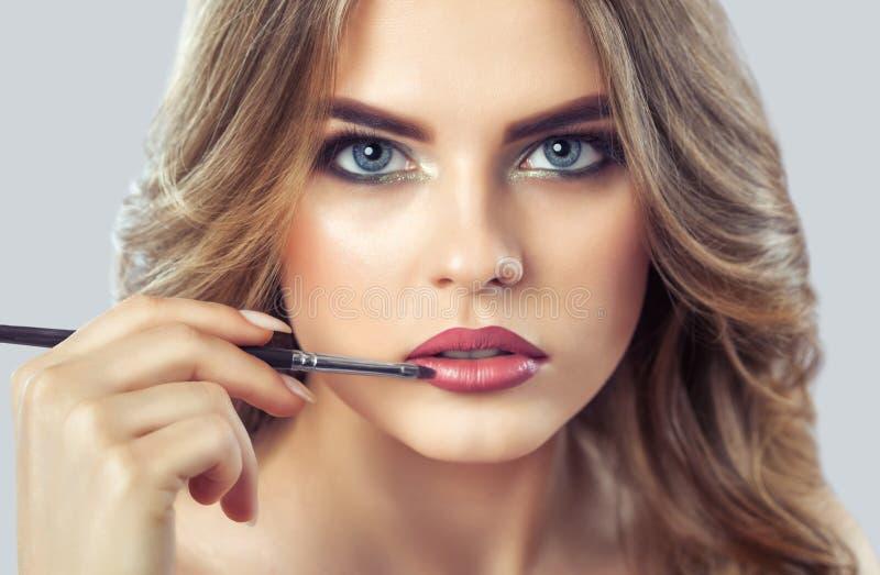 De grimeur schildert de lippen van een mooie vrouw, voltooit samenstelling in de schoonheidssalon royalty-vrije stock foto