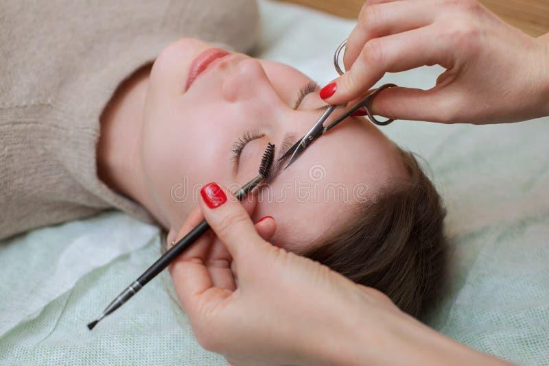 De grimeurkammen en scheren haar brows met schaar aan een mooi jong meisje stock afbeeldingen