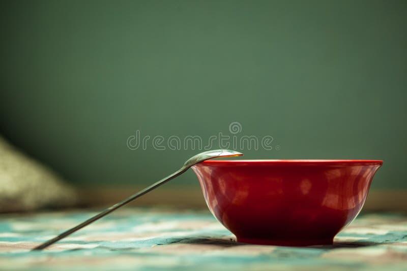 De groene achtergrond van de ontbijttijd, rode kom, ijzerlepel, geruit tafelkleed, natuurlijke licht en plaats in het kader van d stock afbeeldingen