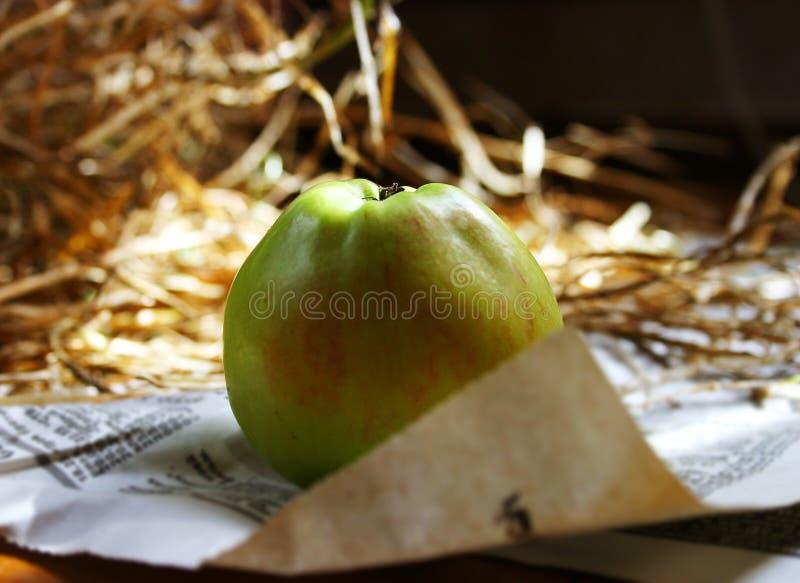 De groene appel ligt op het hooi in de zolder stock foto's