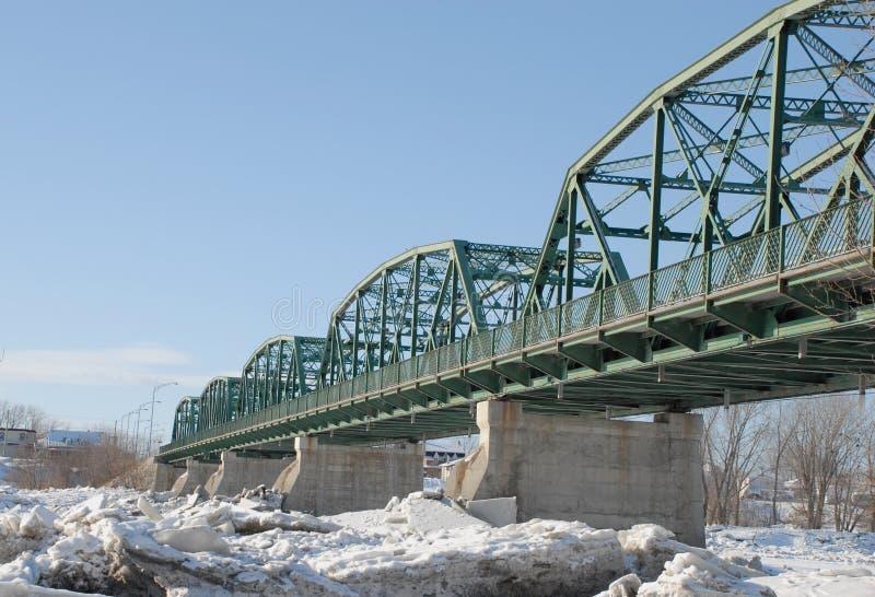 De groene brug van de metaalbundel acorss een bevroren rivier royalty-vrije stock foto's