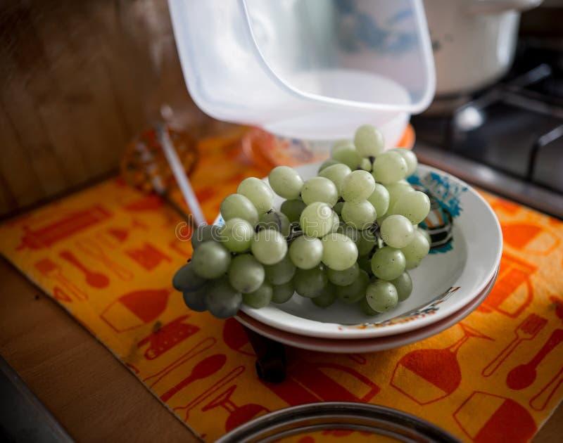 De groene druiven zijn in een schotel die zich in de keuken bevindt royalty-vrije stock afbeelding