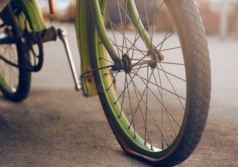 De groene fiets, die zich op het asfalt met een lek band bevinden stock afbeeldingen