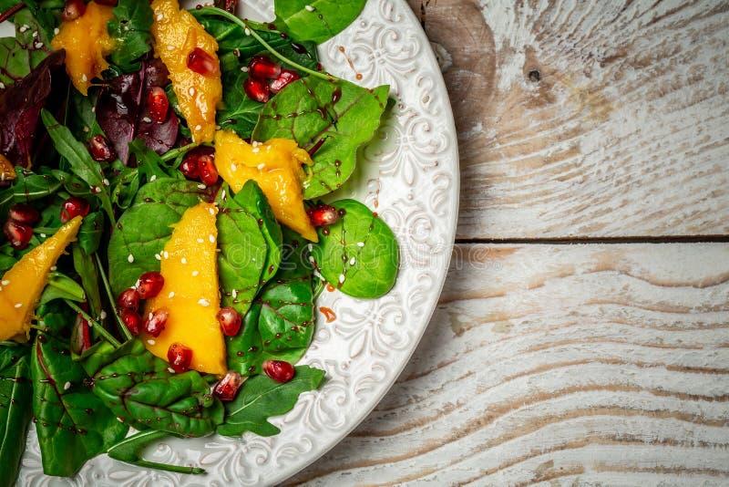 De groene maaltijd van het veganistontbijt in kom met sla, mango, granaatappel en sesam Het schone eten, detox, vegetarisch voeds royalty-vrije stock afbeelding