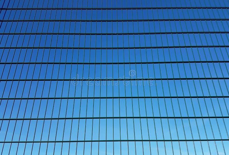 De groene omheining van het metaalnetwerk met vierkante cellen tegen een blauwe hemel Achtergrond van parallelle die lijnen in pe stock afbeelding