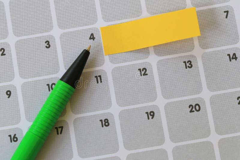 De groene pen richt aan een vier aantal kalender en heeft spatie yel stock afbeeldingen
