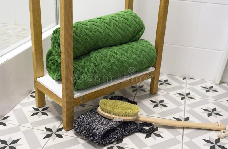 De groene prachtig gevouwen handdoeken op een witte plank met een massage borstelen en washandje royalty-vrije stock foto's