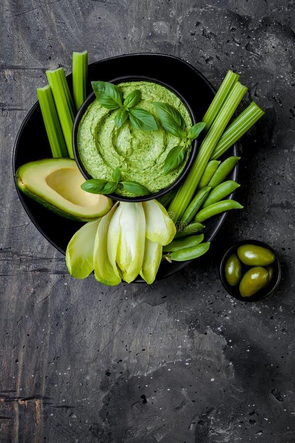 De groene raad van de groentensnack met van kruidhummus of pesto onderdompeling De gezonde ruwe schotel van het de zomervoorgerec stock foto's