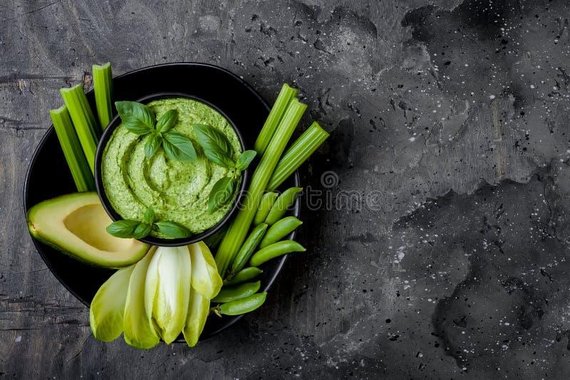 De groene raad van de groentensnack met van kruidhummus of pesto onderdompeling De gezonde ruwe schotel van het de zomervoorgerec stock afbeelding