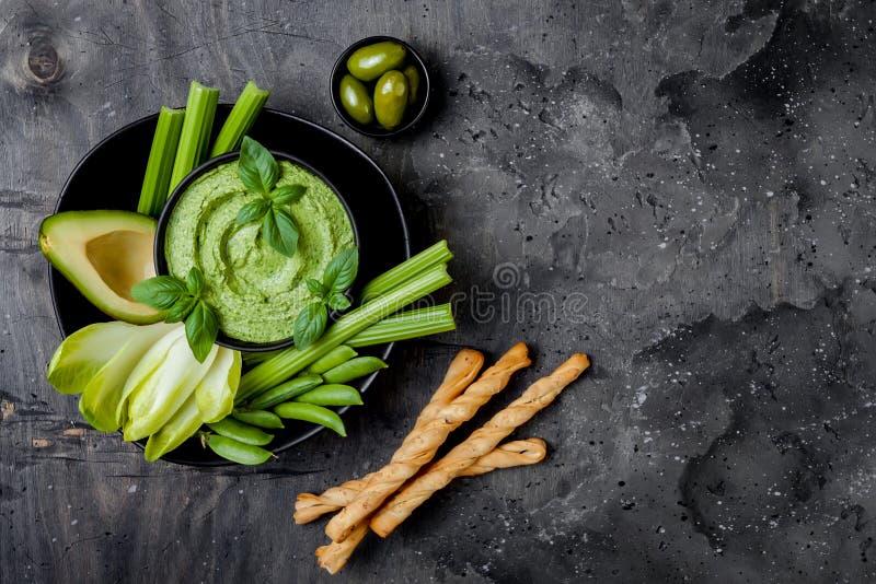De groene raad van de groentensnack met van kruidhummus of pesto onderdompeling De gezonde ruwe schotel van het de zomervoorgerec stock fotografie