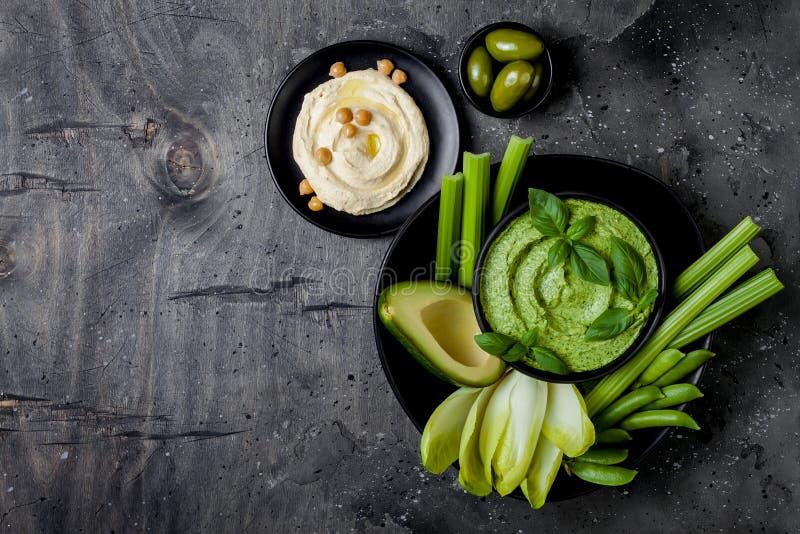 De groene raad van de groentensnack met van kruidhummus of pesto onderdompeling De gezonde ruwe schotel van het de zomervoorgerec stock afbeeldingen