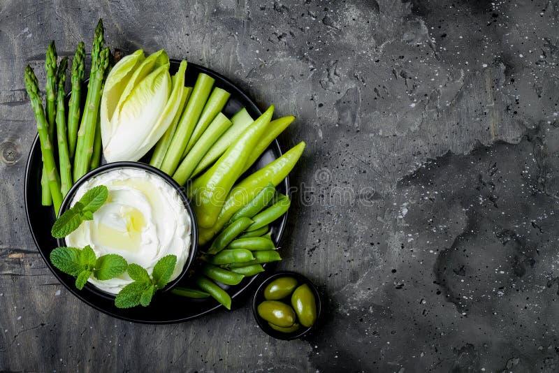 De groene raad van de groentensnack met yoghurtsaus of labneh onderdompeling Gezonde ruwe de zomerschotel royalty-vrije stock afbeelding