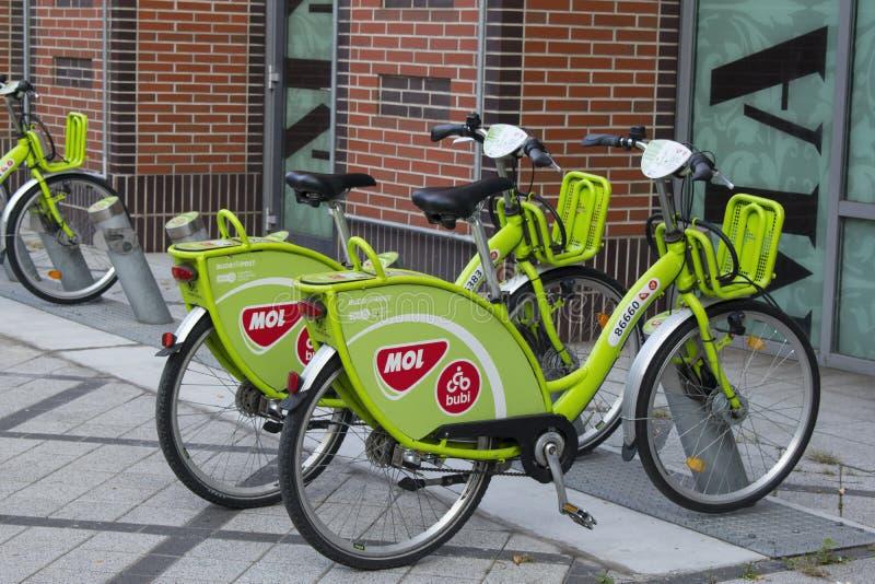De groene rentable fietsen van MOL Bubi naast Westend-Stadscentrum, in de straat van VÃ ¡ ci stock afbeeldingen