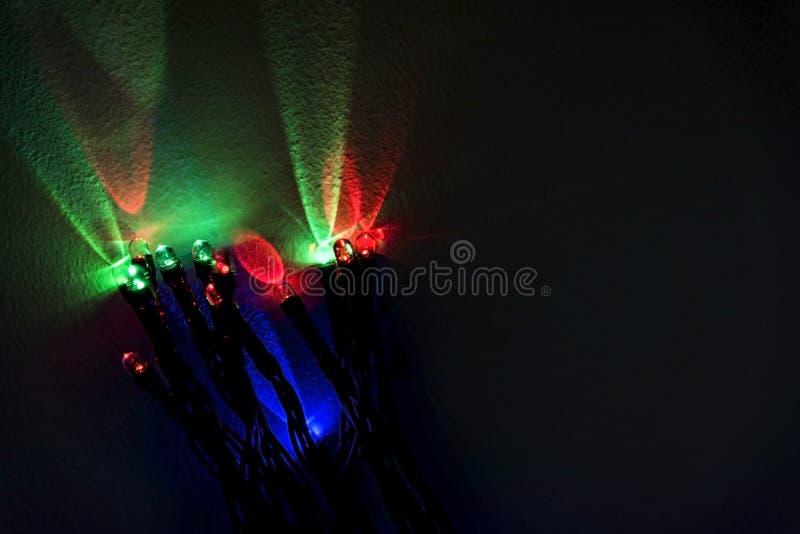 De groene, rode en blauwe bezinningen van Kerstmislichten over een witte Muur voor decoratie, sluiten omhoog stock foto