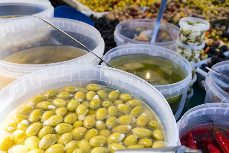 De groene, rode en zwarte olijven, Spaanse pepers, bewaart in een Franse markt in Parijs Frankrijk stock fotografie