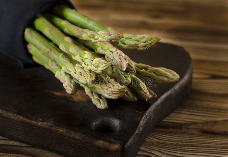 De groene sappige asperge ligt op een houten raad op een bruine houten lijst stock foto's