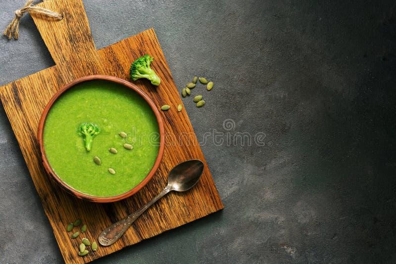 De groene soep van roombroccoli met pompoenzaden in een ceramische kom op een knipselraad, donkere rustieke achtergrond Hoogste m stock afbeelding