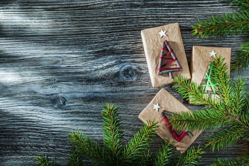 De groene sparrentakken pakten huidige doos op houten raad in stock fotografie