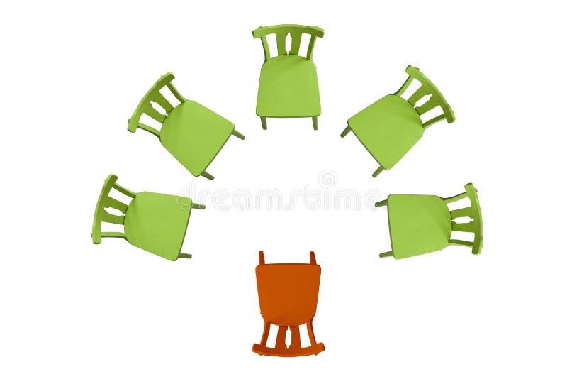 De groene stoelen bevinden zich op een witte achtergrond in een halve cirkel, één oranje stoel, hoogste geïsoleerde meningsachter stock illustratie