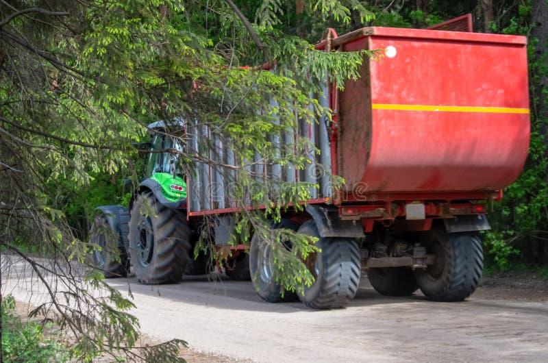 De groene tractor draagt een rode aanhangwagen stock foto
