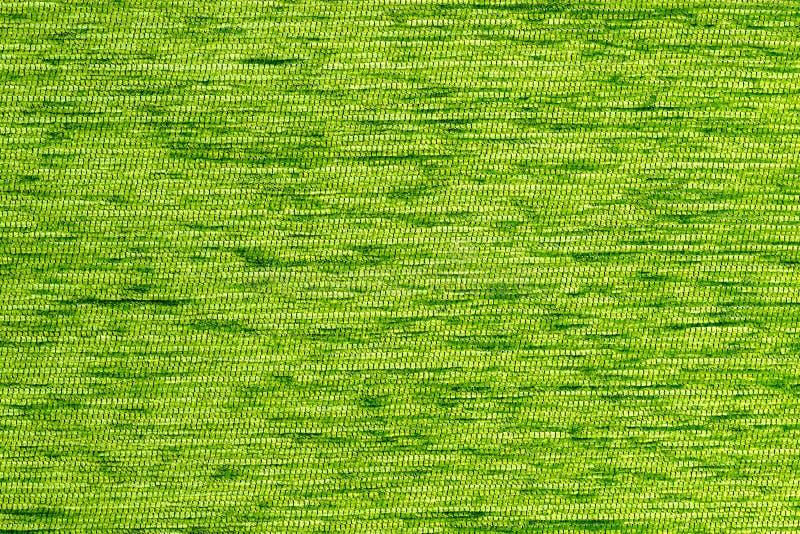 De groene vlakke korte harde achtergrond van de pluis dichte stof, sluit omhoog zonder enige het vertroebelen stock afbeelding